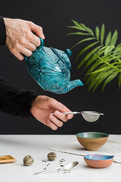 Mężczyzna Nalewanie Herbaty W Kości Przez Sitko Darmowe Zdjęcia