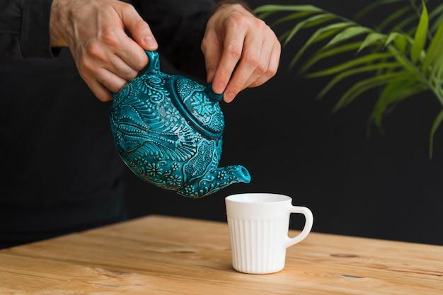Mężczyzna Nalewanie Herbaty W Kubek Darmowe Zdjęcia