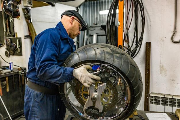 Mężczyzna naprawiający oponę motocyklową z zestawem naprawczym, zestaw naprawczy zaślepki do opon bezdętkowych. Premium Zdjęcia