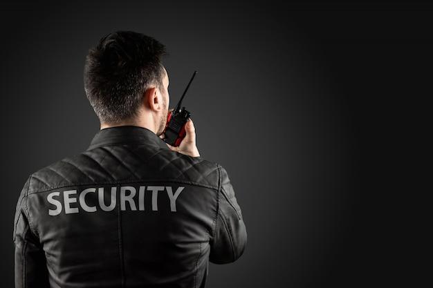 Mężczyzna, ochrona, trzyma walkie-talkie. Premium Zdjęcia