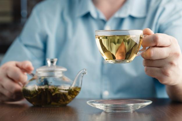 Mężczyzna Oferuje Filiżankę Herbaty Premium Zdjęcia