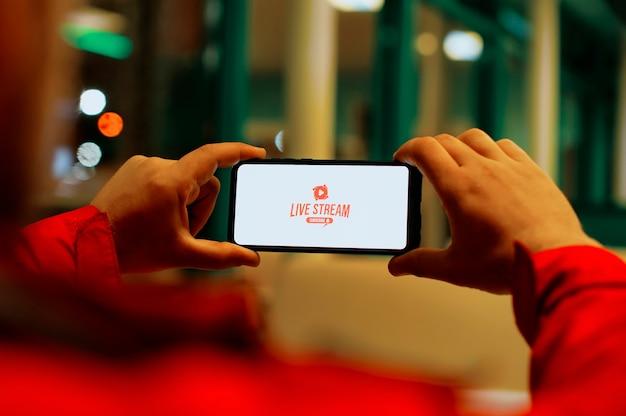 Mężczyzna Ogląda Transmisję Na żywo Na Ekranie Smartfona. Przycisk Transmisja Na żywo Na Ekranie Telefonu Komórkowego. Premium Zdjęcia