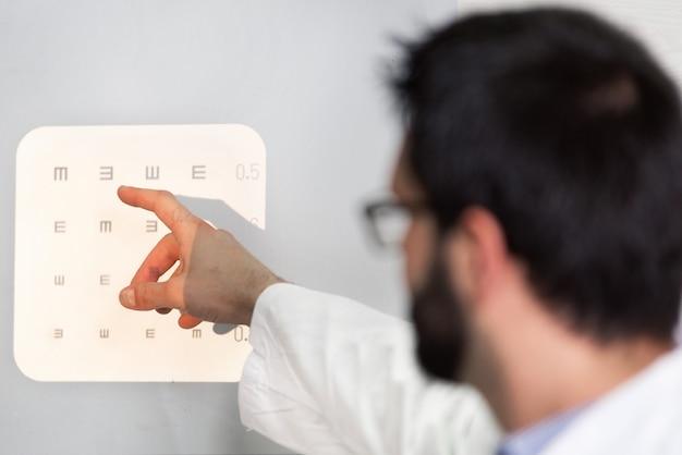 Mężczyzna Okulista, Wskazując Na Litery Wykresu Oka. Premium Zdjęcia