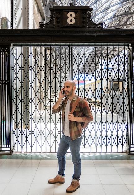 Mężczyzna Opowiada Nad Telefonem Z Plecakiem Darmowe Zdjęcia