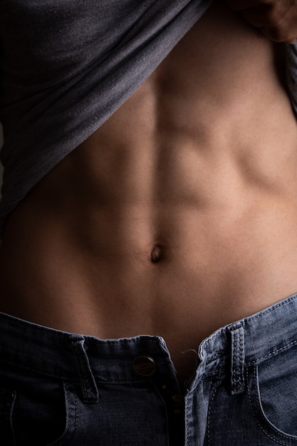 Mężczyzna otworzył koszulkę, aby pokazać prasę brzucha Premium Zdjęcia