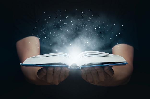 Mężczyzna Otworzył Magiczną Książkę Z Rosnącymi światłami I Magicznym Proszkiem. Koncepcja Uczenia Się I Edukacji Premium Zdjęcia