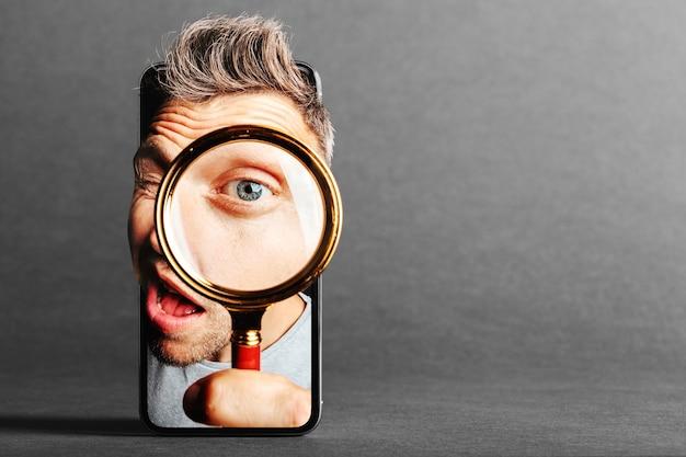 Mężczyzna Patrzy W Lupę Przez Telefon Komórkowy Premium Zdjęcia