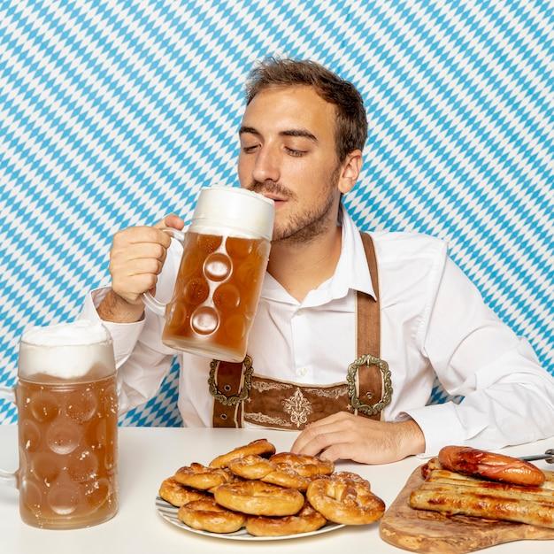 Mężczyzna Pije Piwo Z Niemieckim Jedzeniem Darmowe Zdjęcia