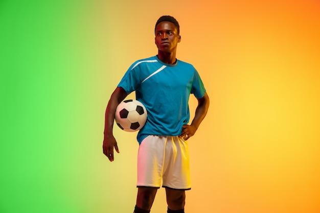 Mężczyzna Piłka Nożna, Piłkarz Trening W Akcji Na Białym Tle Na Gradientu Studio W świetle Neonu Darmowe Zdjęcia