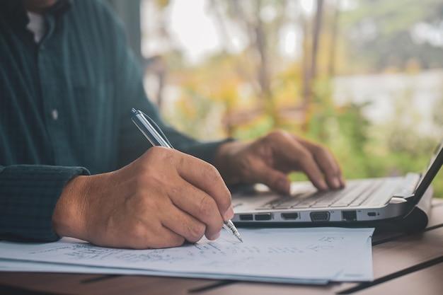 Mężczyzna Pisać Na Maszynie Na Laptopie I Pisze Na Papierach Premium Zdjęcia