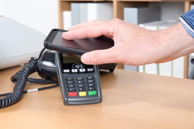 Mężczyzna płaci na dobre dzięki technologii nfc na telefonie komórkowym Premium Zdjęcia
