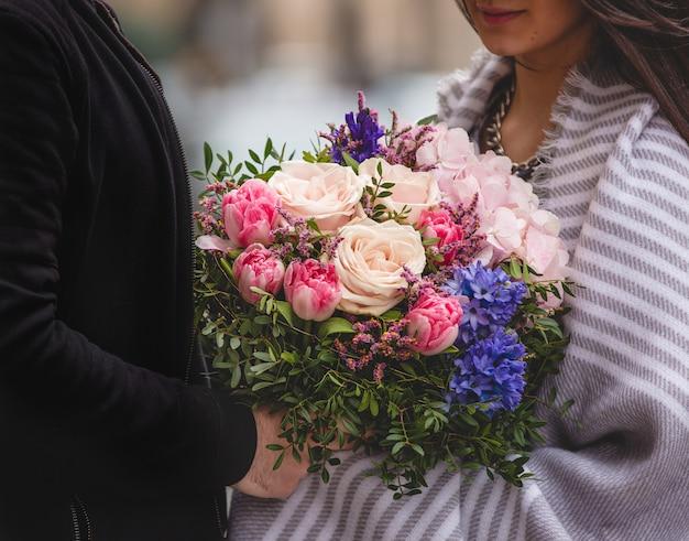 Mężczyzna podając kobiecie bukiet kwiatów mieszanych Darmowe Zdjęcia