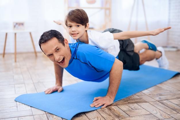 Mężczyzna podnosi się z podłogi z chłopcem na plecach. Premium Zdjęcia