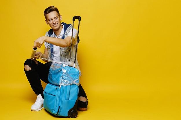 Mężczyzna Podróżujący Z Walizką Przygotowuje Go Do Oddania Do Bagażu Podczas Odprawy Na Lotnisku Premium Zdjęcia