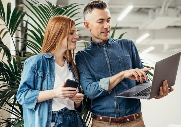 Mężczyzna Pokazuje Coś Na Laptopie Swojemu Współpracownikowi Darmowe Zdjęcia