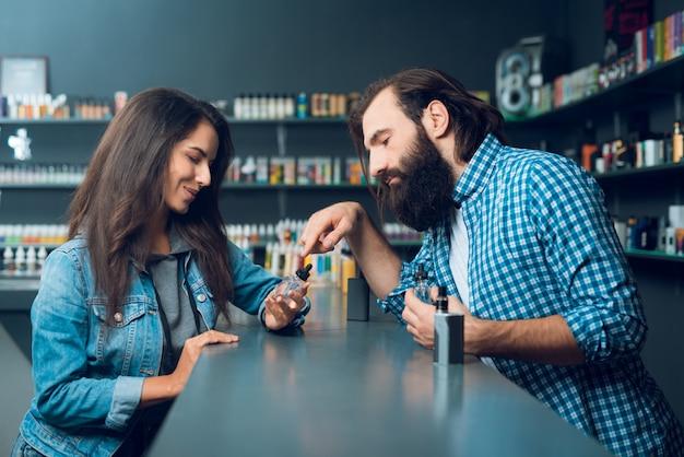 Mężczyzna Pokazuje Kobiecie, Jak Wypełnić Sos Papierosowy. Premium Zdjęcia