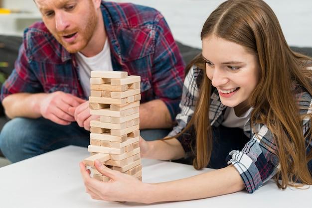 Mężczyzna Poważnie Patrząc Na Uśmiechniętą Dziewczynę Usuwa Drewniane Klocki Z Wieży Darmowe Zdjęcia