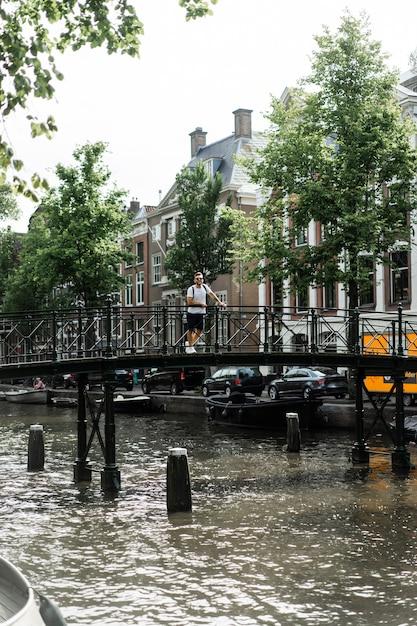 Mężczyzna pozowanie na moście w amsterdamie. Darmowe Zdjęcia