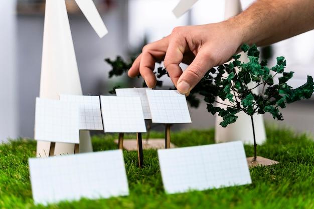 Mężczyzna Pracujący Nad Ekologicznym Układem Projektu Energii Wiatrowej Z Turbinami Wiatrowymi Premium Zdjęcia