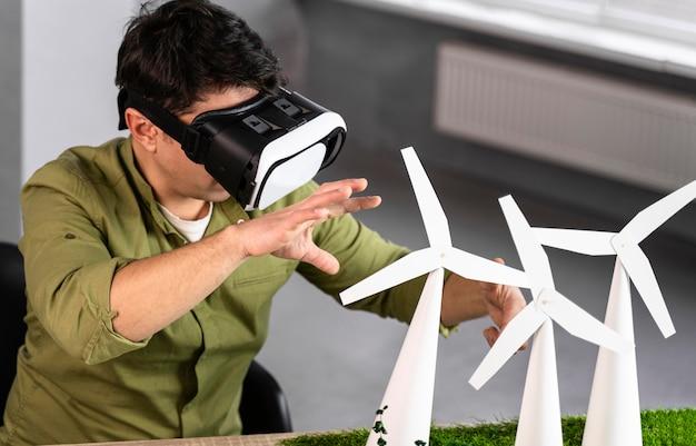 Mężczyzna Pracujący Nad Projektem Ekologicznej Energii Wiatrowej Przy Użyciu Zestawu Słuchawkowego Do Rzeczywistości Wirtualnej Darmowe Zdjęcia