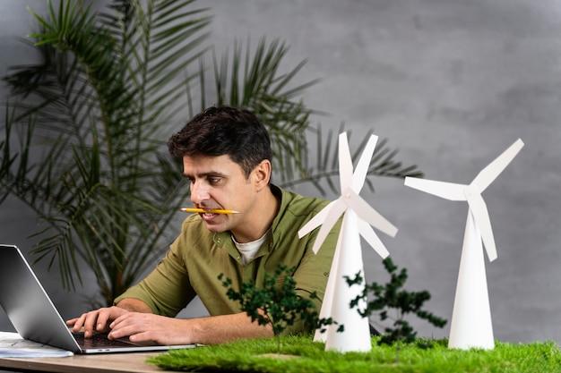 Mężczyzna Pracujący Nad Projektem Ekologicznej Energii Wiatrowej Z Turbinami Wiatrowymi I Laptopem Darmowe Zdjęcia