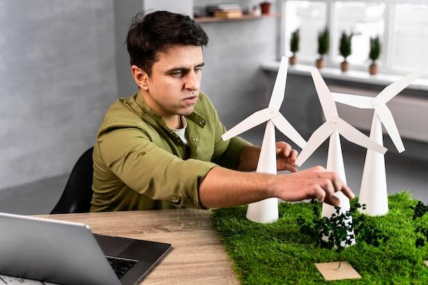 Mężczyzna Pracujący Nad Projektem Ekologicznej Energii Wiatrowej Z Turbinami Wiatrowymi Darmowe Zdjęcia
