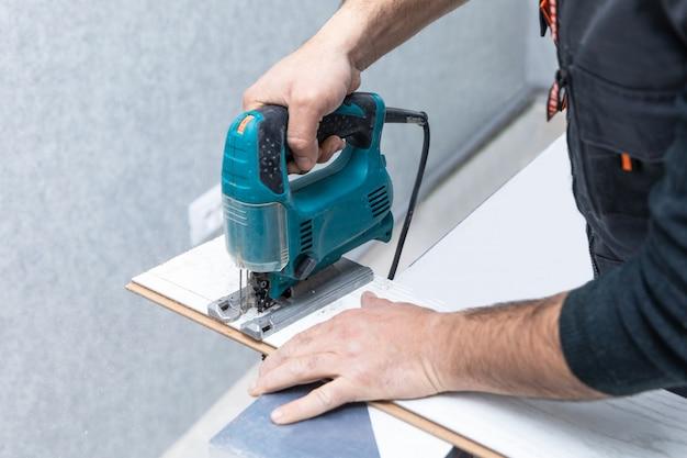 Mężczyzna Pracujący Z Wyrzynarką Na Białym Laminacie Drewnianym Premium Zdjęcia