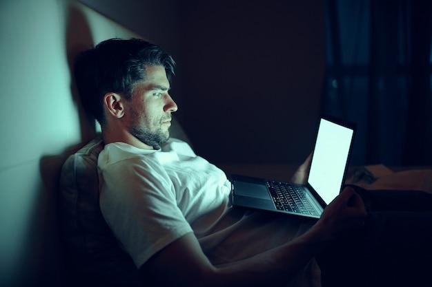 Mężczyzna Pracuje Na Laptopie W łóżku, Ukochana Kobieta śpi, Praca W Nocy, Zdrada Premium Zdjęcia
