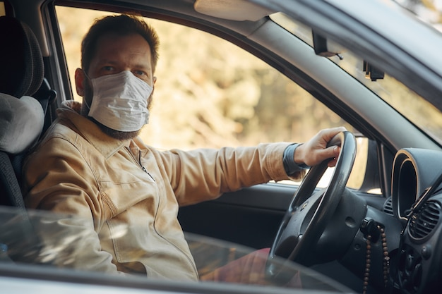 Mężczyzna Prowadzący Samochód Podczas Epidemii Zakłada Maskę Medyczną Premium Zdjęcia