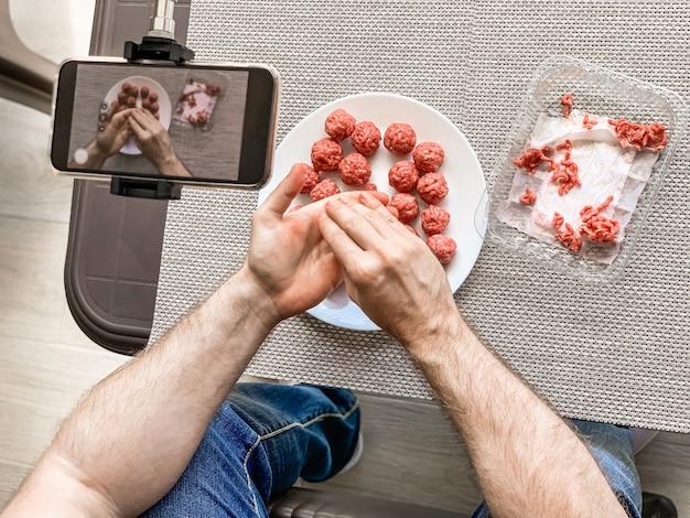 Mężczyzna Ręce Przygotowuje Klopsiki Z Surowego Mięsa Mielonego Nagrywania Wideo Na Smartfonie. Styl życia Z Bliska Kompozycja Z Naturalnym światłem. Domowe Gotowanie Vlogger Influencer Streaming Koncepcja Blogowania Premium Zdjęcia