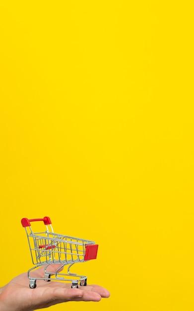 Mężczyzna Ręka Trzyma Mały Wózek Na Zakupy Na żółtym Tle. Premium Zdjęcia