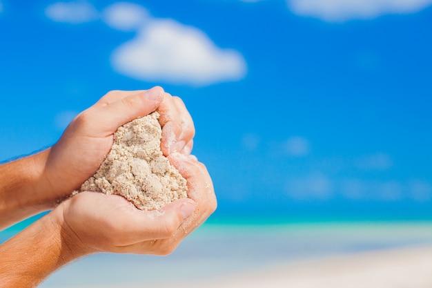 Mężczyzna Ręki Trzyma Białej Tropikalnej Plaży Formy Kierowego Kształta Tło Morze Premium Zdjęcia