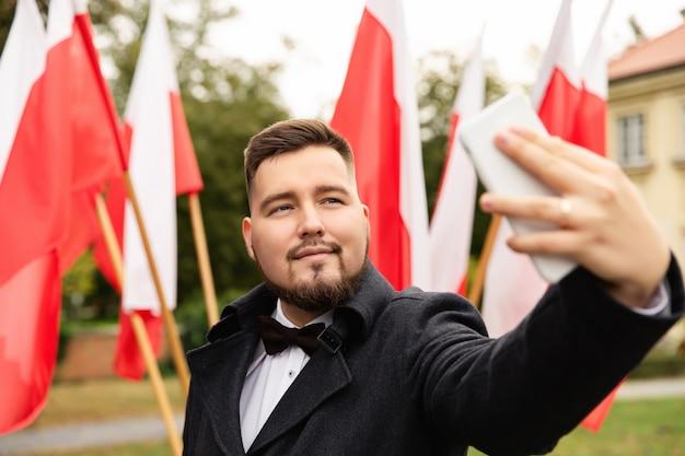 Mężczyzna Robi Selfie Z Flagami Polski Z Tyłu Premium Zdjęcia