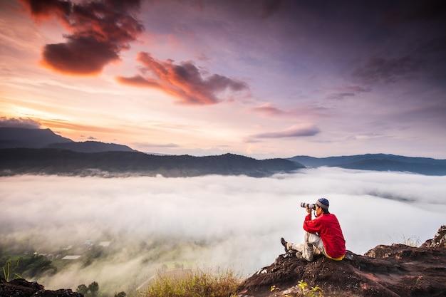 Mężczyzna robi zdjęcia morza mgły na wysokiej górze. Premium Zdjęcia