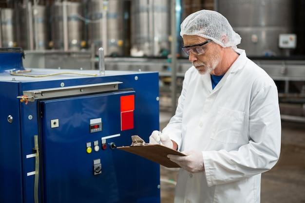 Mężczyzna Robotnik Kontrolujący Maszyny W Fabryce Zimnych Napojów Darmowe Zdjęcia