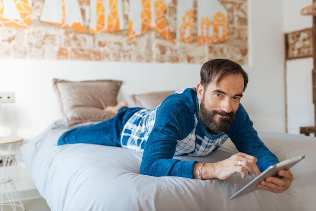 Mężczyzna Siedzący W łóżku Zrelaksowany W Domu Na Stole Premium Zdjęcia