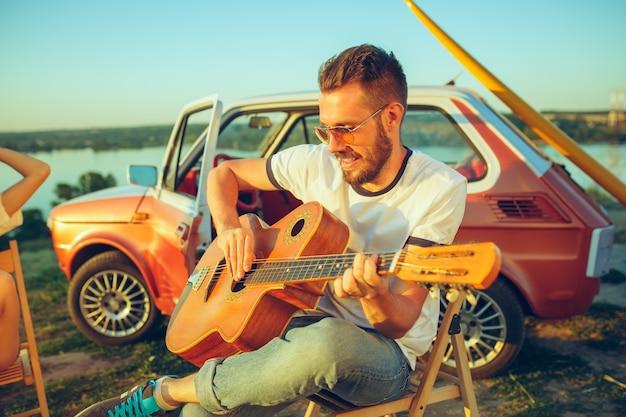 Mężczyzna Siedzi I Odpoczywa Na Plaży, Grając Na Gitarze W Letni Dzień, W Pobliżu Rzeki. Wakacje, Podróże, Koncepcja Lato. Darmowe Zdjęcia