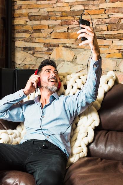 Mężczyzna Siedzi Na Kanapie Ze Słuchawkami Na Uszach, Nawiązując Połączenie Wideo Przez Smartfon Darmowe Zdjęcia