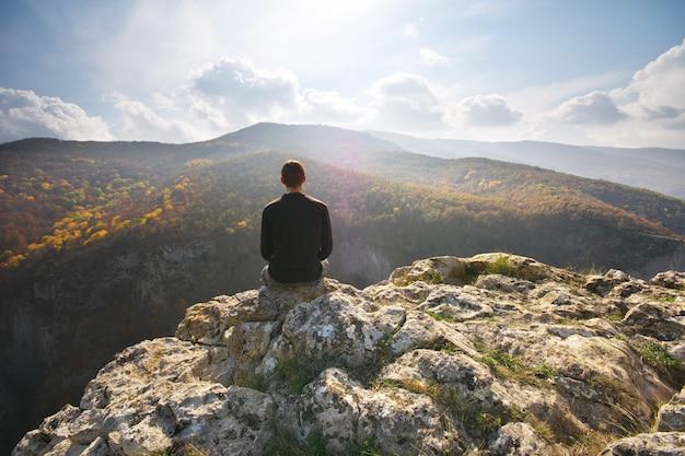 Mężczyzna Siedzi Na Klifie Góry. Premium Zdjęcia