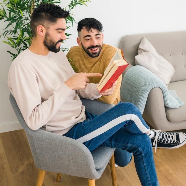 Mężczyzna Siedzi Na Krześle Pokazując Coś Na Książki Do Swojego Chłopaka Darmowe Zdjęcia