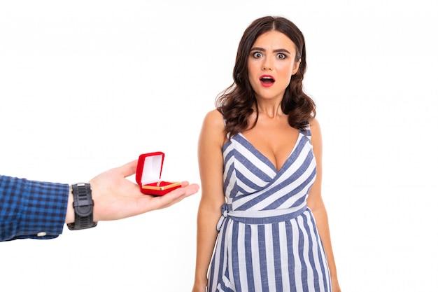 Mężczyzna Składa Dziewczynie Propozycję I Daje Pierścionek I Zaskoczoną Dziewczynę W Sukience Na Białej ścianie Premium Zdjęcia