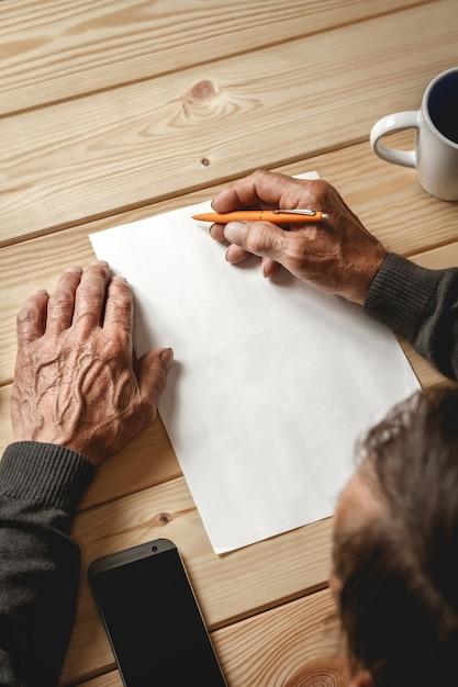 Mężczyzna Stare Ręce Pisze Na Pustej Kartce Papieru Premium Zdjęcia