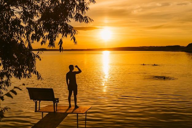 Mężczyzna stoi na murze w pobliżu jeziora i patrzy na zachód słońca. Premium Zdjęcia