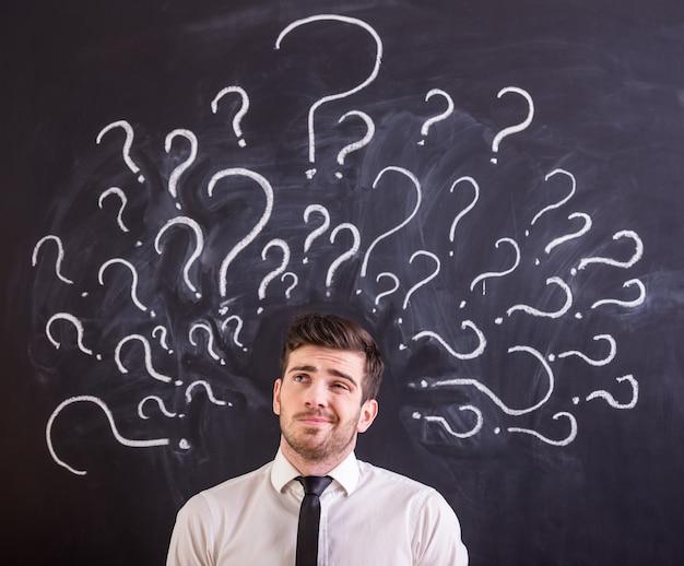Mężczyzna stoi przeciw blackboard z znakami zapytania. Premium Zdjęcia