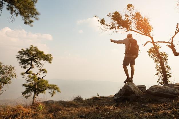 Mężczyzna Stojący Na Klifie W Dolinie I Górach. Premium Zdjęcia