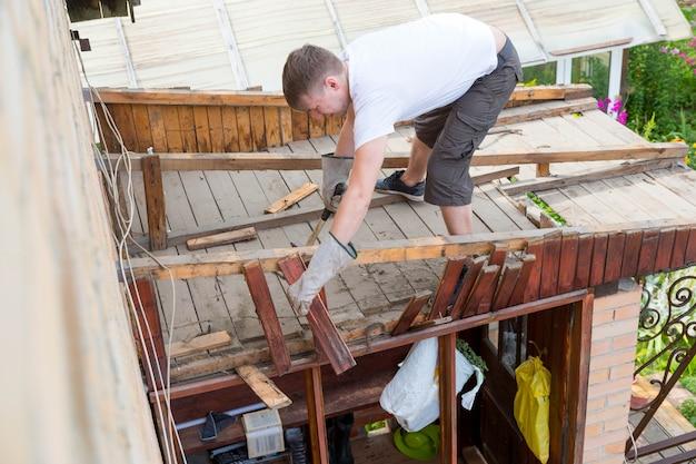 Mężczyzna Stuka Starą, Zgniłą Drewnianą Deskę Młotkiem Z Parsowania Dachu Premium Zdjęcia