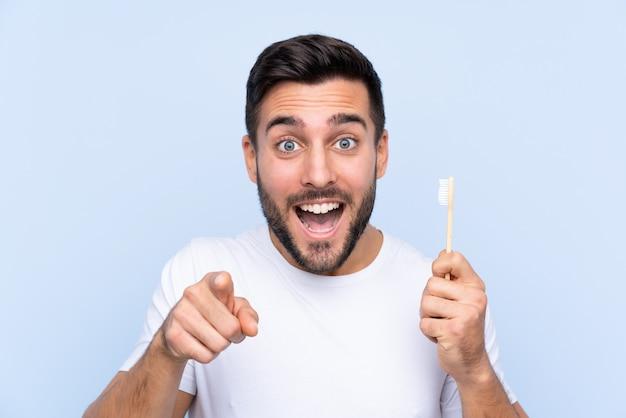 Mężczyzna Szczotkuje Jego Zęby Nad Odosobnioną ścianą Z Brodą Premium Zdjęcia