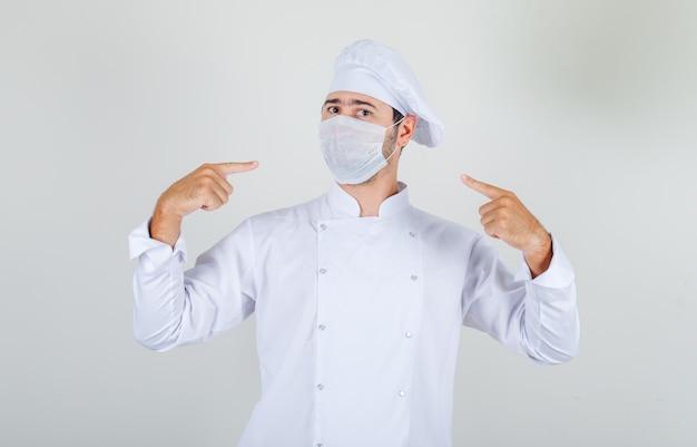 Mężczyzna Szefa Kuchni, Wskazując Palcami Na Maskę Medyczną W Białym Mundurze I Patrząc Uważnie Darmowe Zdjęcia