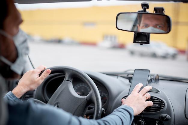 Mężczyzna Taksówkarz W Masce Medycznej Wsiada Do Samochodu I Włącza Nawigatora Na Swoim Smartfonie Premium Zdjęcia