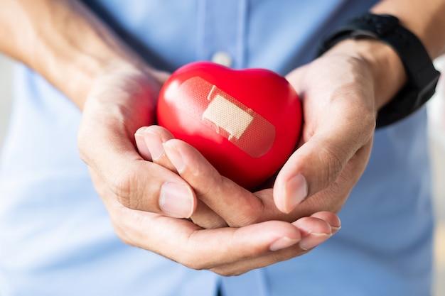 Mężczyzna trzyma czerwonego kierowego kształt na drewnianym tle. opieka zdrowotna, ubezpieczenie na życie Premium Zdjęcia